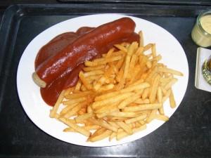 Cârnăciori Currywurst serviţi cu cartofi prăjiţi şi ketchup